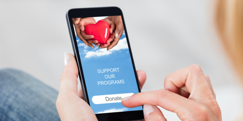A woman donates on her smartphone as part of an online fundraising effort.